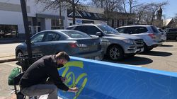 """Newton-based artist Harun Zankel paints the word """"together"""" onto a jersey barrier in Newton Centre."""