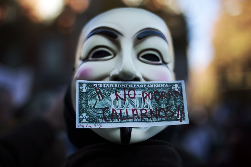 """Occupy: A protester in Spain wore a Guy Fawkes mask, symbolic of the hacktivist group """"Anonymous."""" The words on the bill read """"We won't be silenced."""""""