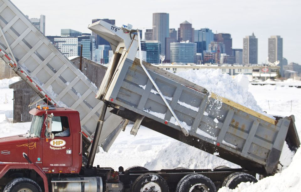 """Dump trucks moved the snow from the streets to the """"snow farm."""""""