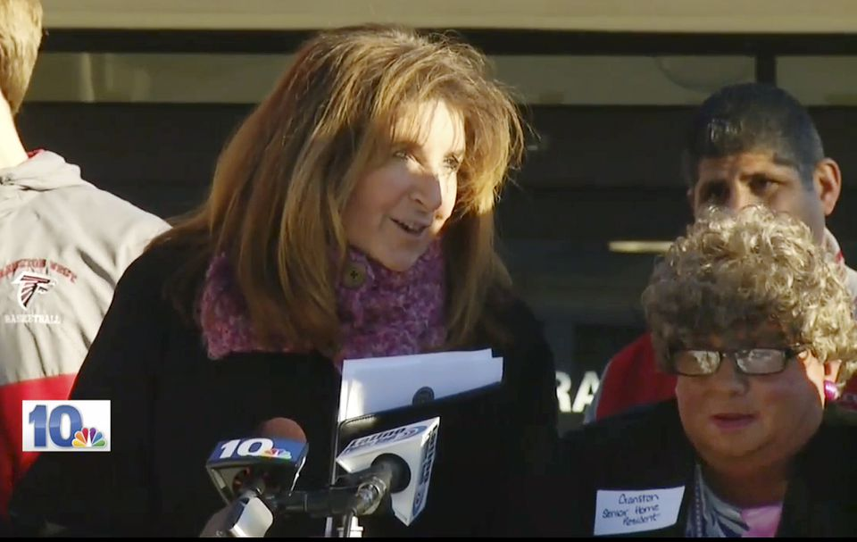 Sue Stenhouse (left) spoke next to a man dressed as an elderly woman (right) during a news conference on Jan. 5 in Cranston, R.I.