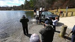 People watch as two workers with the Massachusetts Division of Fisheries and Wildlife release 900 rainbow trout into Forest Lake in Methuen in March.