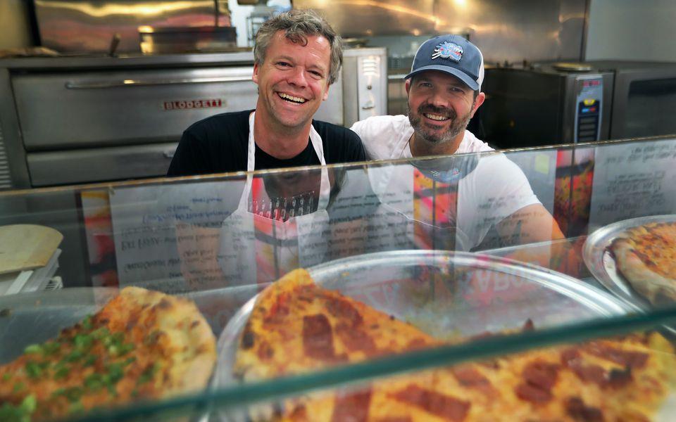 Charlie Redd (left) and Keenan Langlois serve up pizza and kabobs in Somerville's Davis Square.