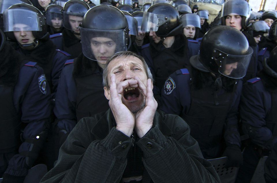 A pro-Russian protester shouts slogans in front of Ukrainian riot police in central Donetsk last month. International issues color the International Monetary Fund's world outlook.