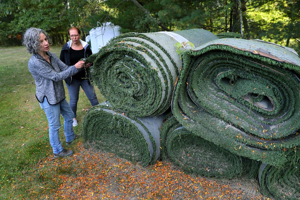 Kyla Bennett (left) and Tracy Stewart of Medway looked over a pile of turf in Franklin.DAVID L RYAN/GLOBE STAFF/GLOBE STAFF