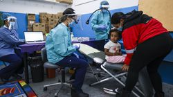 ForsythKids dentist Helen Nguyen talks to 2-year-old Emma Alvarez before her dental examination while her mother Grace Duran stands nearby in October 2020. Since dental services were cut off when schools closed, programs like ForsythKids, which runs a mobile school-based dental program in Lynn and other parts of the state, set up outside of community centers, including the Lynn Boys and Girls Club.