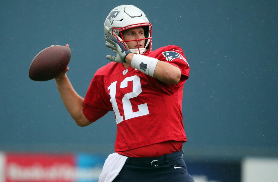 Tom Brady limbers up at training camp Sunday at the Gillette Stadium practice field.