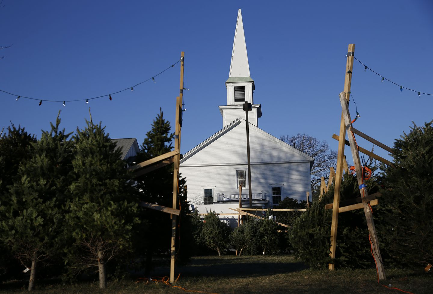 Christmas trees are for sale in front of the United Church of Christ, Congregational in Boxborough.