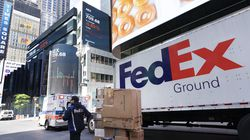 A FedEx driver delivers a cart of packages in New York.