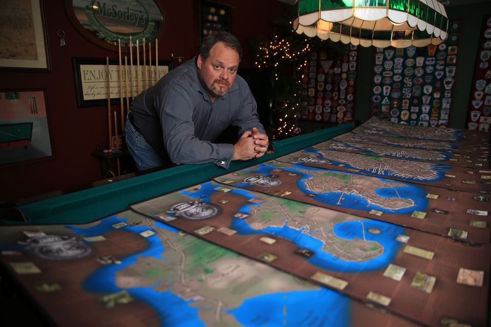 Ed McCarthy is seen with his maps in his basement.