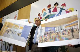 Architect Andy Jonic holds artists' renderings showing the BPL group the planned renovation of the children's room and addition of a teen center.