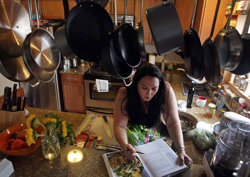 """Gayle Squires is using a recipe from """"Jerusalem"""" (and notating it) to make lunch in her Cambridge kitchen for a friend."""