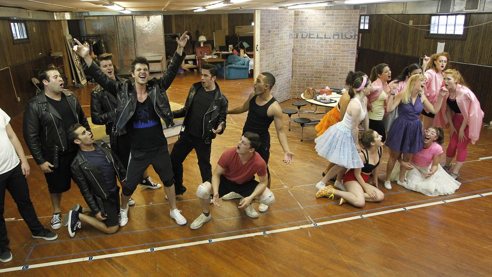 """The cast of the Theatre by the Sea production of """"Grease"""" rehearses in front of a sparse set. The real set was created by designer Nate Bertone."""