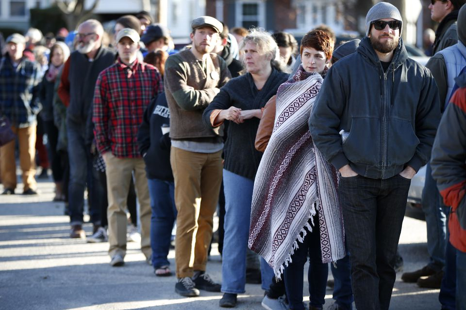 Voters, some of whom waited more than five hours, stood in a line that stretched well over one-half mile to get into a Democratic caucus location at Deering High School in Portland, Maine, on Sunday.