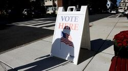 A man cast his shadow on a sign outside of a polling place in Everett on Tuesday.