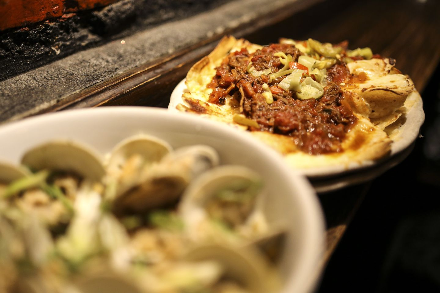 Italian nachos are crisp corn chips topped with braised short-rib ragu, ricotta, and pepperoncini.