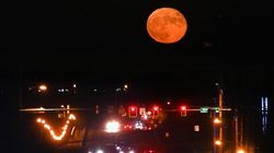 A nearly full moon rises over the main drag that leads to Stillwater Medical Center in Stillwater, Okla., Sept.21, 2021.