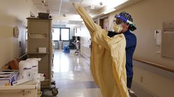 """A registered nurse dons protective gear before entering a room at a hospital in Royal Oak, Mich. In 2021, U.S. hospitalizations and deaths are nearly all among the unvaccinated, and real-world data from Britain and Israel support that protection against the worst cases remains strong. What scientists call """"breakthrough"""" infections in people who are fully vaccinated make up a small fraction of cases."""