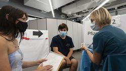 Anissa Barbato, left, discusses the Pfizer COVID-19 vaccine with Jolanta Gawlik before her son Samuel, center, is vaccinated, Friday, July 30, 2021 in New York.