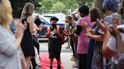 Sixth-grader Angel Montilla laughs as he makes his way down the line of teachers and staff at the Academy of the Pacific Rim Charter Public School in Hyde Park, holding their annual Red Carpet First Day of School Welcome, on Aug. 30.