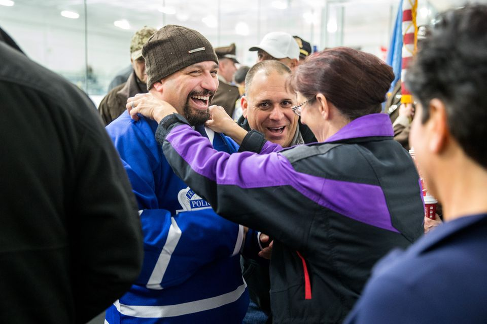 Officer Richard Cintolo got an assist from his wife, Sharon, while donning a hockey jersey before the start of a game between the Boston Police team and the Boston Bruins alumni team.