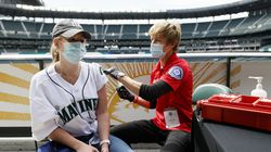Sydney Porter received her COVID-19 vaccination from Kristine Gill, with the Seattle Fire Department's Mobile Vaccination Teams, before the game between the Seattle Mariners and the Baltimore Orioles at T-Mobile Park on May 5 in Seattle. As demand for the vaccine slows, Major League Baseball is heavily promoting inoculations, and stadiums have become a new line of demarcation, where vaccinated sections are highlighted as perks akin to VIP skyboxes.