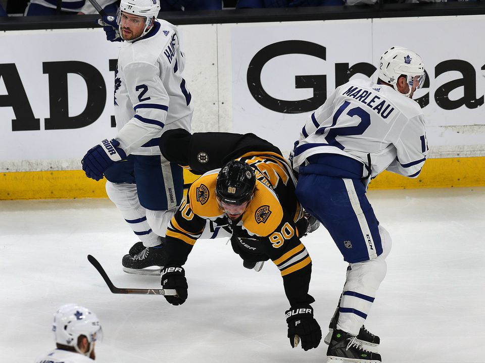 Marcus Johansson was sandwiched by Leafs Ron Hainsey (left) and Patrick Marleau in the first period.