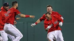 Rafael Devers is chased down by his teammates after his game-winning RBI single Monday night.
