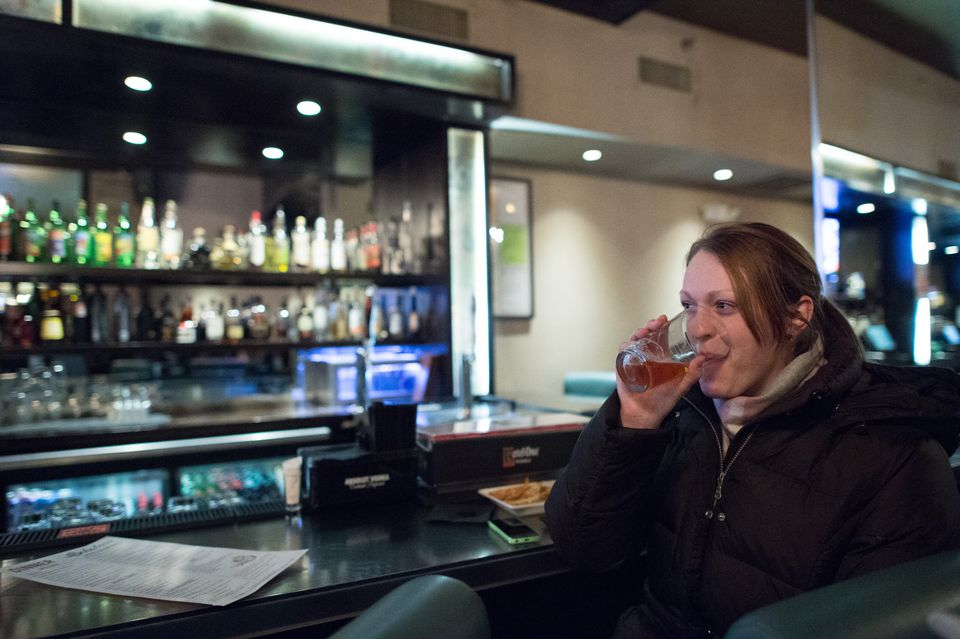 Elise Anderson, 29, of Chelsea, consumes a drink after work recently at Scholars American Bistro & Cocktail Lounge in Boston. Anderson said that she once worked at a company where staff members — who worked long hours — often drank wine on Friday afternoons.