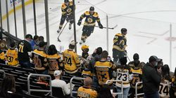 Fans gather near the glass at TD Garden to watch Boston Bruins players warm up before an NHL hockey game against the New York Islanders, Monday, May 10, 2021, in Boston. Massachusetts has moved to the next step in its COVID-19 reopening plan, allowing large indoor and outdoor venues, including TD Garden, Fenway Park, and Gillette Stadium to increase fan capacity from 12% to 25%.