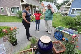 Charlene DiCalogero, center, confers with neighbors at Camelot CoHousing, a development engineered to encourage friendship and community involvement.