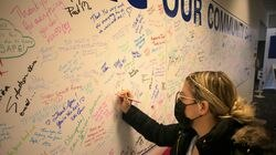 Alysia Bryant wrote a message on the community wall as she left the Lowell General Hospital mass vaccination site at the Cross River Center last week.