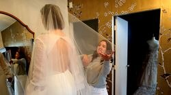 Courtney Lefferts models a wedding dress at Glo Bridal in Newton as Molly Wolfberg Swarttz, the shop's owner, helps with the veil.