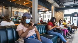 Lauren Jackson wears a face mask while sitting inside a Starbucks in New York on Tuesday, July 27, 2021. Revising a decision made just two months ago, the Centers for Disease Control and Prevention said on Tuesday that people vaccinated against the coronavirus should resume wearing masks in public indoor spaces in parts of the country where the virus is surging.