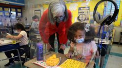 US Representative Katherine Clark and first-grade student Yanelys Canales looked over school work together at a desk with clear plastic shielding at McGlynn Elementary School in Medford on Thursday.