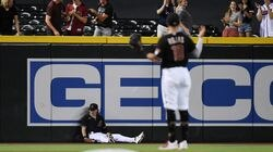 Arizona left fielder Jake McCarthy was down after attempting to climb the wall and catch a drive by Adam Duvall in the first inning.
