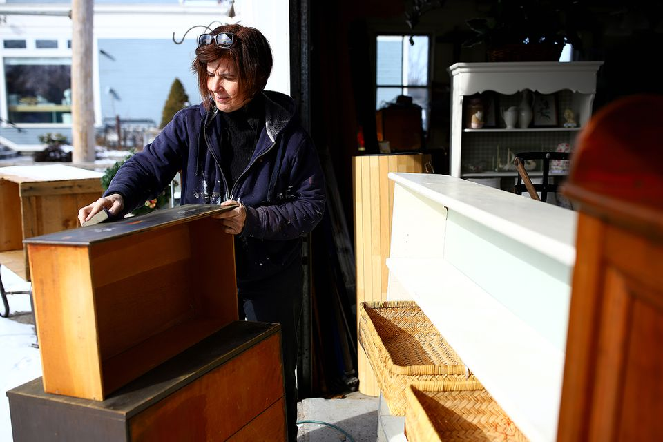 Meg Gaudet sands an older piece of furniture at her store, A New Leaf.