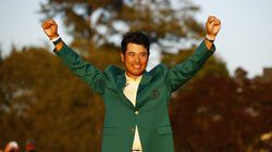 Hideki Matsuyama raises his fists while donning the green jacket after his Masters victory.