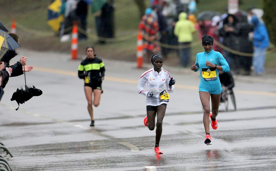 Linden (left) reels in Gladys Chesir (center) and Mamitu Daska (right) on Heartbreak Hill.