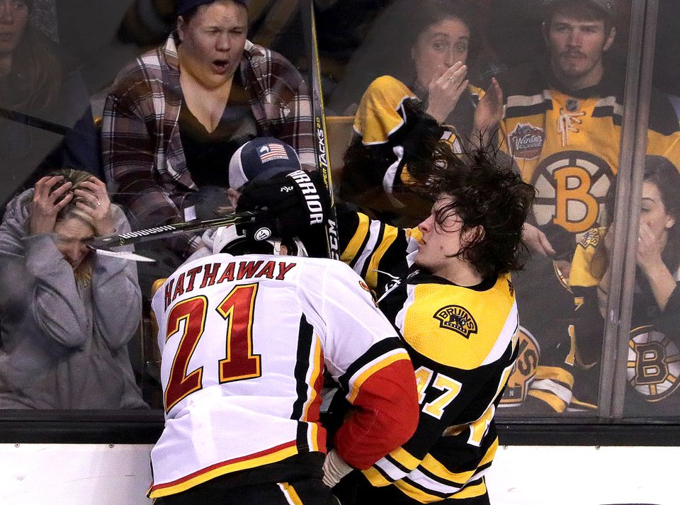 Fans at TD Garden can barely watch as the Flames' Garnet Hathaway checks Torey Krug into the boards during the second period.