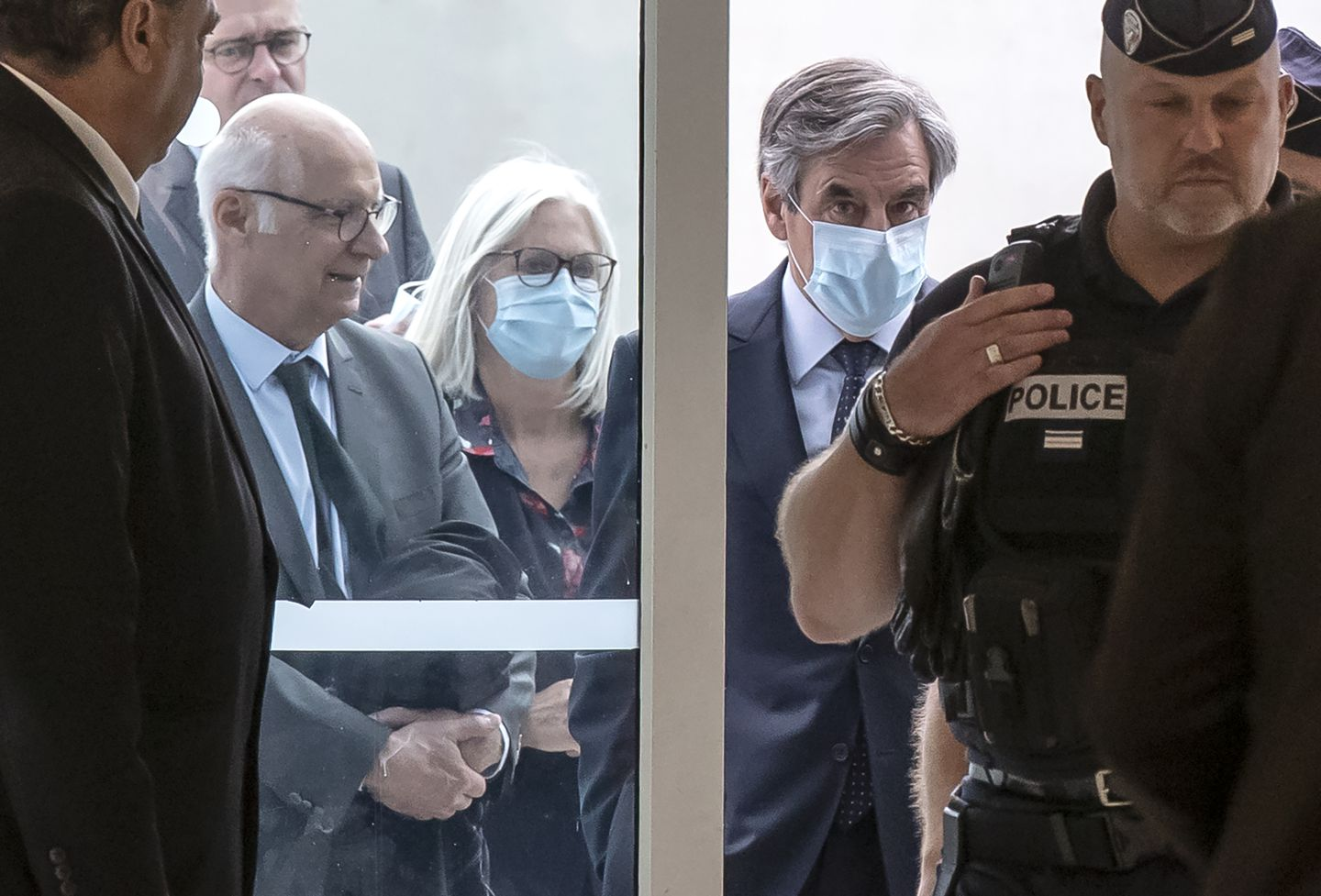 France's former prime minister François Fillon and his wife Penelope wore protective masks as they arrived at the Paris courthouse on Monday.