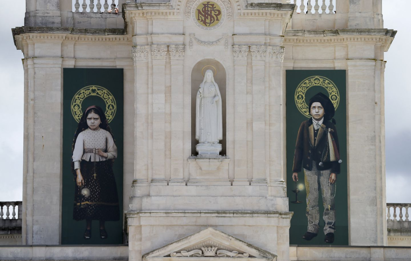 The pictures of Jacinta, left, and Francisco Marto, hang on the facade of the Sanctuary of Our Lady of Fatima.