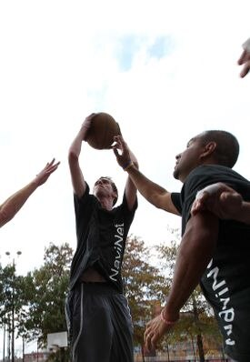 NaviNet's Chris Paine (left) and Frank Figueroa play their weekly basketball game. The company sponsors teams in several sports — including cricket.