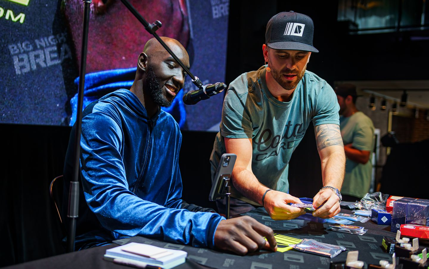 """Celtics fan favorite Tacko Fall """"ripped"""" packs at the Causeway Card Show with Chris Costa, one of the organizers."""