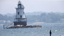A family member stood on the sandbar during the search for the body of 10-year-old girl Yoskarly Martinez in Narragansett Bay in Rhode Island.