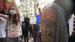 A protester with an image of ousted Myanmar leader Aung San Suu Kyi on their arm joined an anti-coup protest march in Yangon on Saturday.