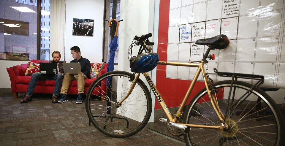 Acorio consultants Sean Duhaime (left) and Max Lim work near CEO Ellen Daley's bicycle.