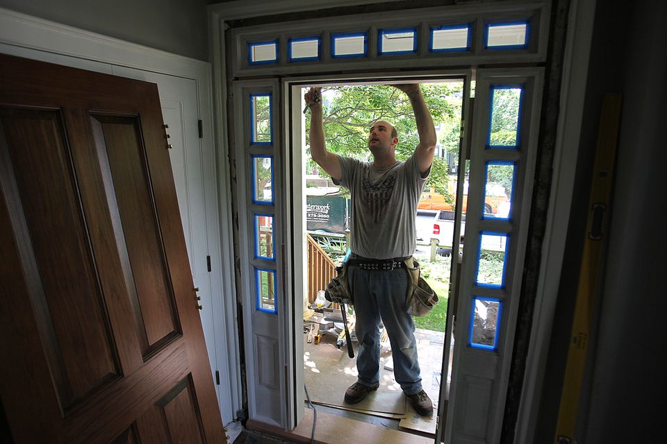Alex Romanowicz worked on a door in Cambridge on a street with many home construction projects under way.