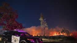 In this Sept. 28. 2020, file photo, a California Highway Patrol officer watched flames visible from the Zogg Fire near Igo, Calif. Pacific Gas & Electric will face criminal charges because its equipment sparked the wildfire that killed four people and destroyed hundreds of homes, a Northern California prosecutor announced Thursday.
