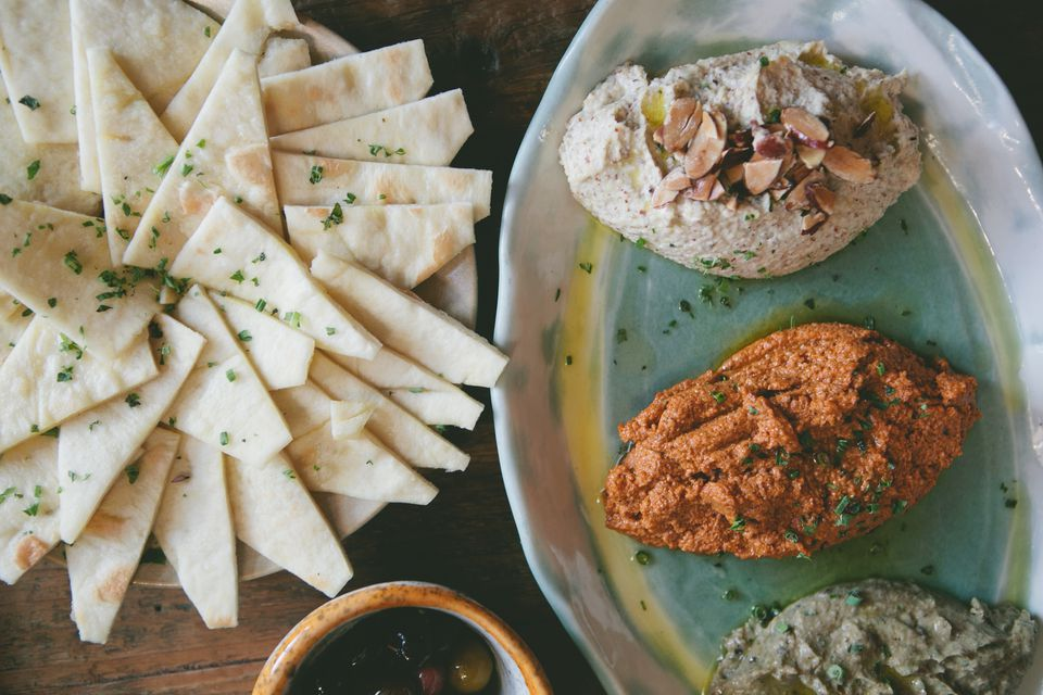 Becker's line of signature dips and spreads includes Middle Eastern flavors such as hummus, smoked eggplant, and tzatziki (top).