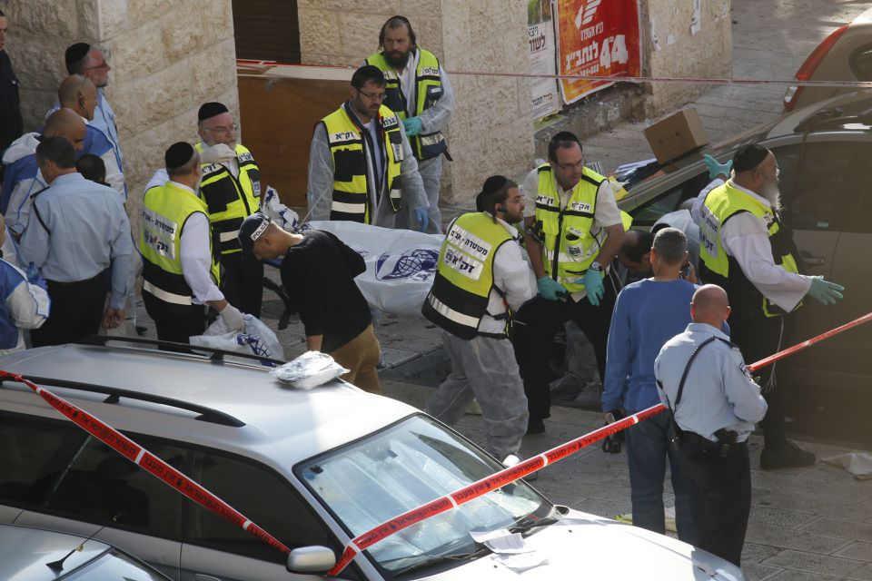 Israeli emergency services volunteers carried the body of a Palestinian assailant who was shot dead while attacking a synagogue in the ultra-Orthodox Har Nof neighborhood in Jerusalem.